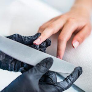 Filing fingernails at nail salon